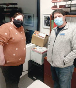 Louis Kuchnir, MD stands with his office manager, Jane, and his shipment of COVID-19 vaccines in elaborate cardboard boxes. He opened a COVID-19 vaccine clinic.