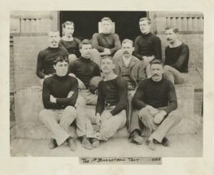 James Naismith (wearing suit) poses with members of the 1892 Springfield College Secretarial Basketball team. This team is sometimes referred to as the first basketball team in existence. (Photo via Springfield College Archives and Special Collections)