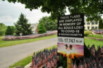 A sign notes the number of deaths due to COVID-19 in Massachusetts as marked by flags on the property of Grafton's Mike Labee.