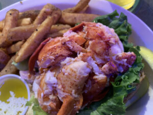 Quahog Republic Dive Bar in Onset's Monsta Lobsta Roll is piled high with perfectly cooked lobster. Quahog Republic Dive Bar is one of Cape Cod's destinations for best lobster rolls. Photo/Sandi Barrett