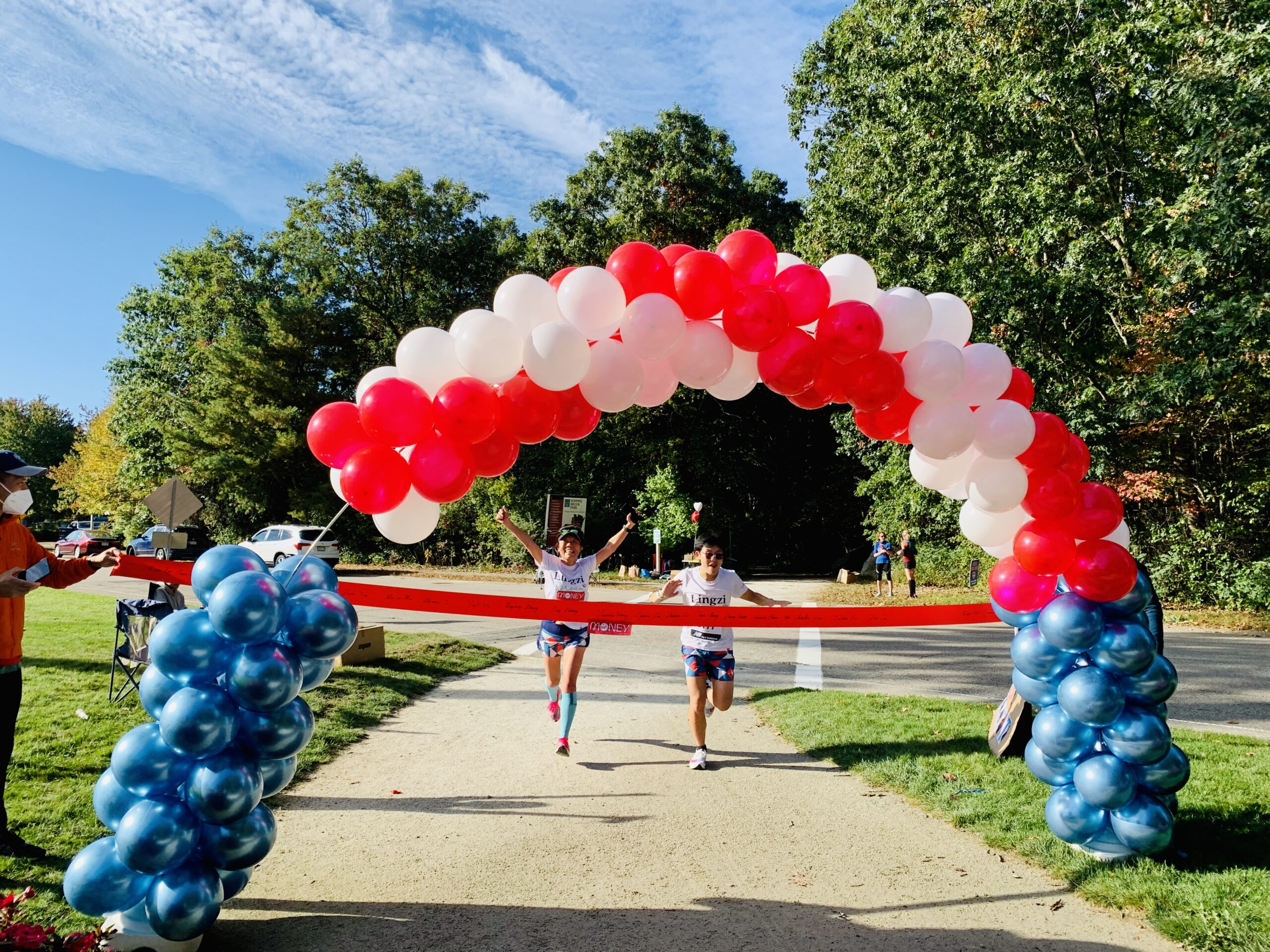 Connie Cao completes the 2020 London Virtual Marathon. Her son, Enchee Xu runs toward the finish line with his mother to complete his first 1/2 marathon.