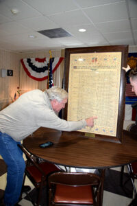 Bob Lord and Matty Sargent find the line for Ralph J. Lord, listing his birth and death, on a recently rediscovered calligraphy piece that notes local World War I service histories.