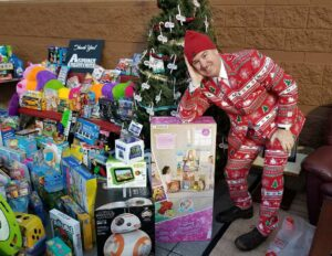 """Tom McAuliffe II of MyFM Media displays donations to MyFM's """"Tailgating for Toys"""" for children who otherwise might not get holiday gifts."""