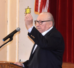 """Israel Arbeiter holds up a """"Jude"""" badge, a star of David that Jewish people were forced to wear under the Nazi regime. """"Jude"""" is German for Jew. Photo/Courtesy of Friends of March of the Living"""