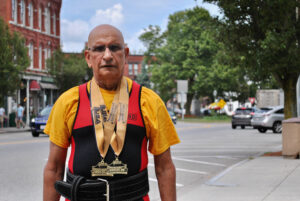 Harmesh Sharma stands near downtown Westborough wearing his powerlifting medals.