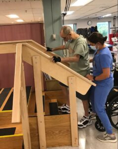 Ralph practices climbing stairs during his rehabilitation program as a staff member assists.
